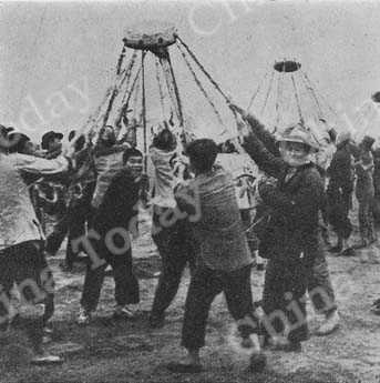 Workers swinging 220-lb. stones to compact earthwork in the traditional Chinese way. Later there will be machines to do this.