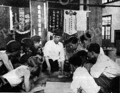 Ma Heng-chang and his team discuss production plan. The banners behind them were won in nationwide work competitions.